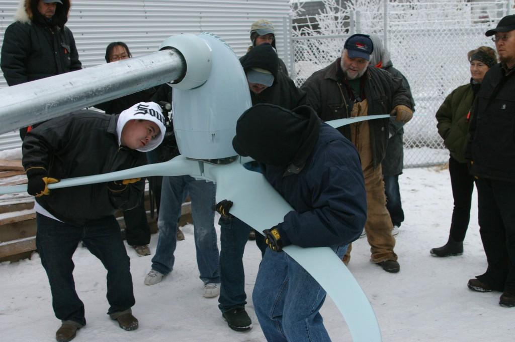 Des hommes se préparent à installer une turbine éolienne (© AP Images)