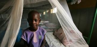 Un enfant souriant, assis sur un lit couvert d'une moustiquaire (AmRefHealth)