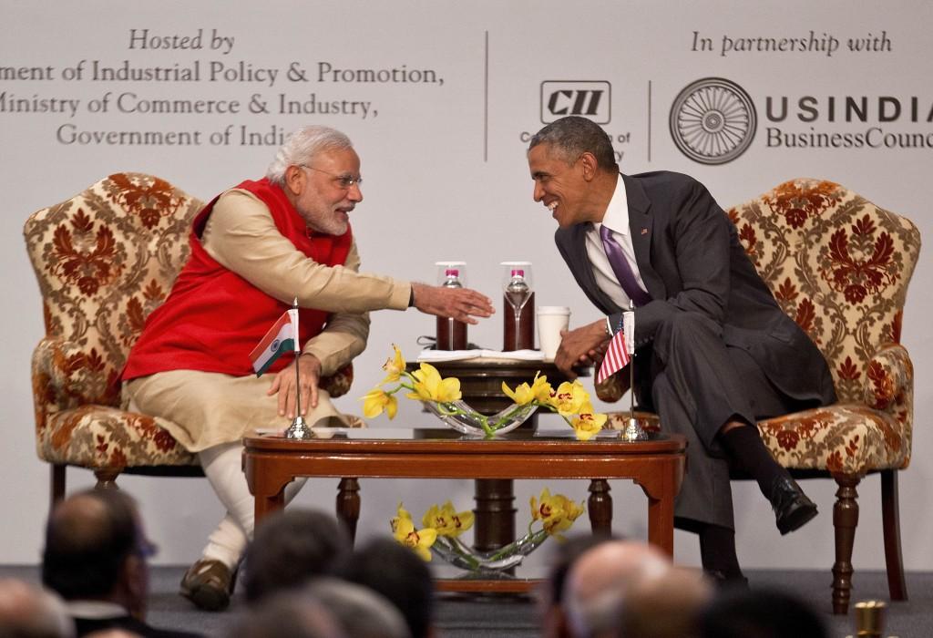 Le Premier ministre indien Narendra Modi et le président américain Obama assis autour d'une table, sourient et s'apprêtent à se serrer la main. (© AP Images)