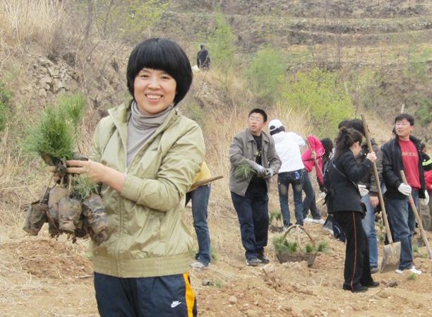 Une femme souriante, des plants d'arbres à la main ; des gens tenant des pelles en arrière-plan. (Alcoa)