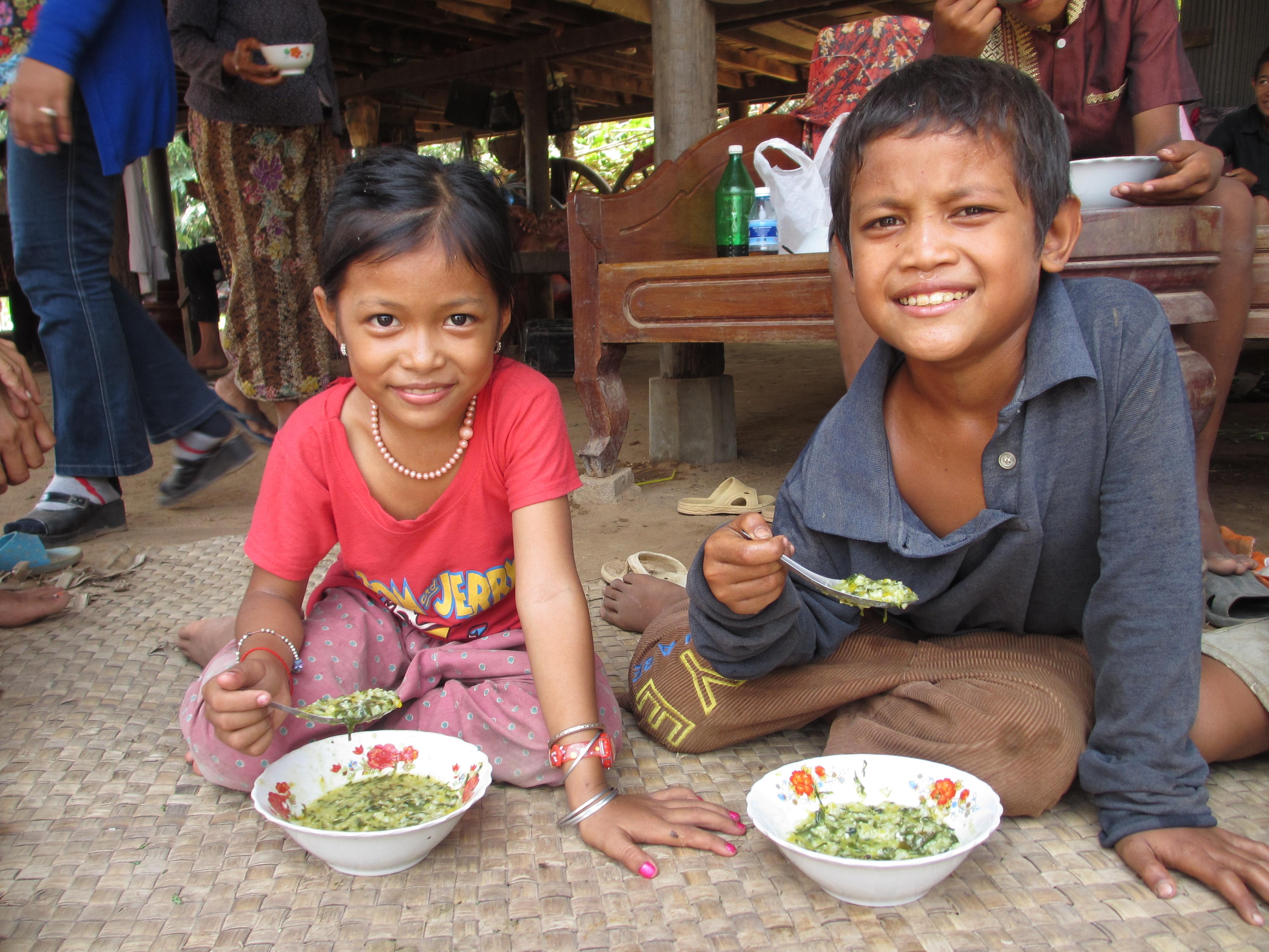 طفلان يأكلان من أطباق على حصيرة (Flickr/USAID/Cambodia HARVEST)