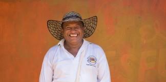 یک مرد خندان با کلاهی که لبه پهن دارد نزدیک یک دیوار گلی (Flickr/USAID)