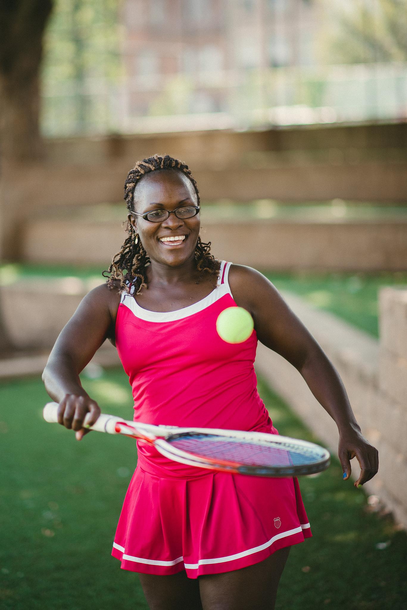 Une femme souriante tenant une raquette et une balle de tennis (Département d'État et Université du Tennessee)