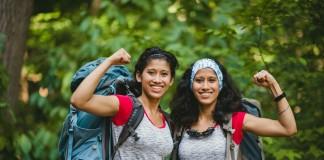 Dos mujeres que llevan mochilas y levantan los puños (Departamento de Estado y Universidad de Tennessee)
