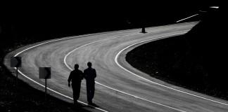 Dos personas caminan en una carretera (© AP Images)