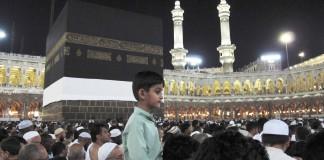 在沙特阿拉伯麦加的朝觐人群中,一名男孩骑在父亲的肩膀上(© AP Images)