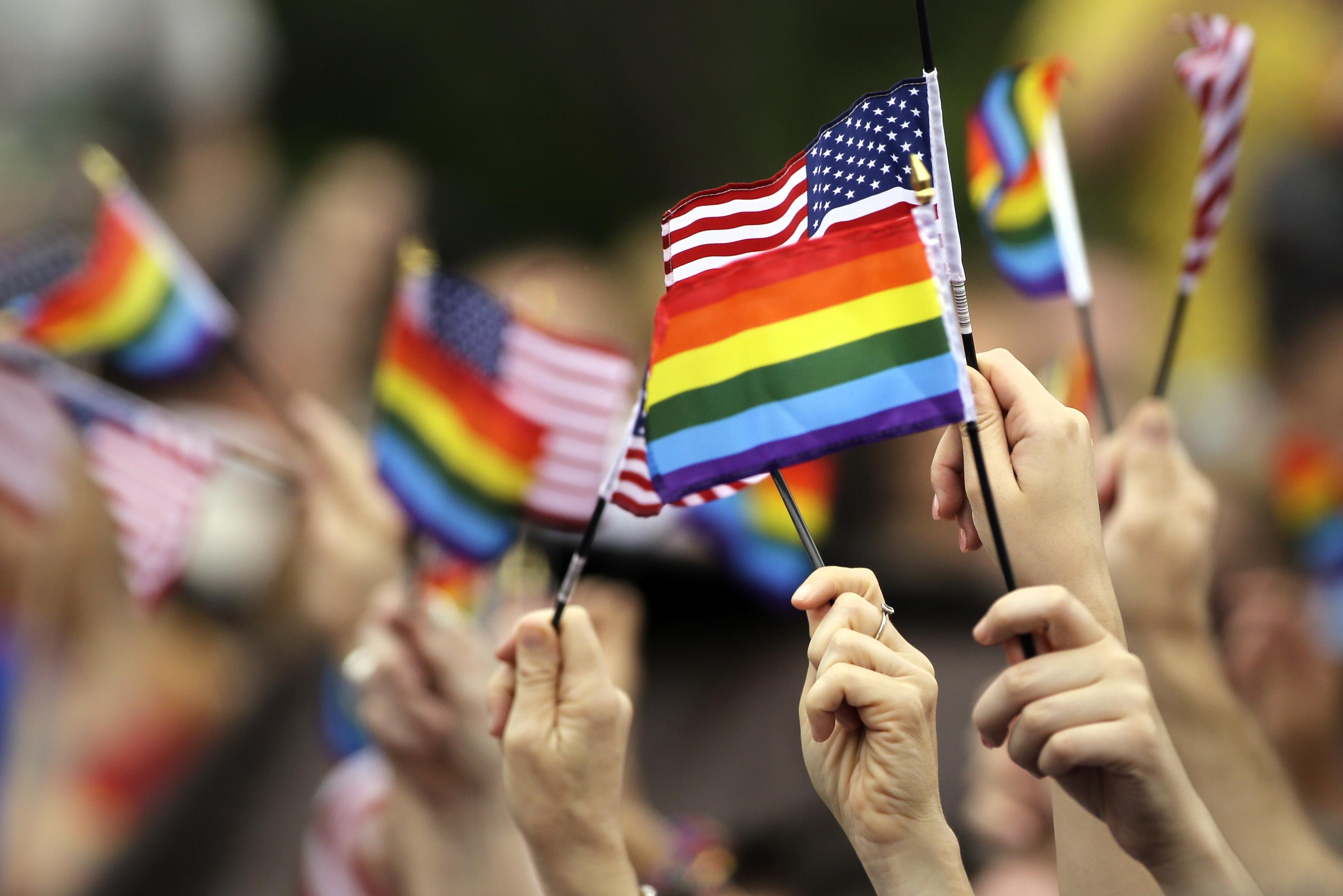دست هایی که در روز استقلال پرچم ایالات متحده و پرچم رنگین کمان را تکان می دهند. (عکس از آسوشیتدپرس)