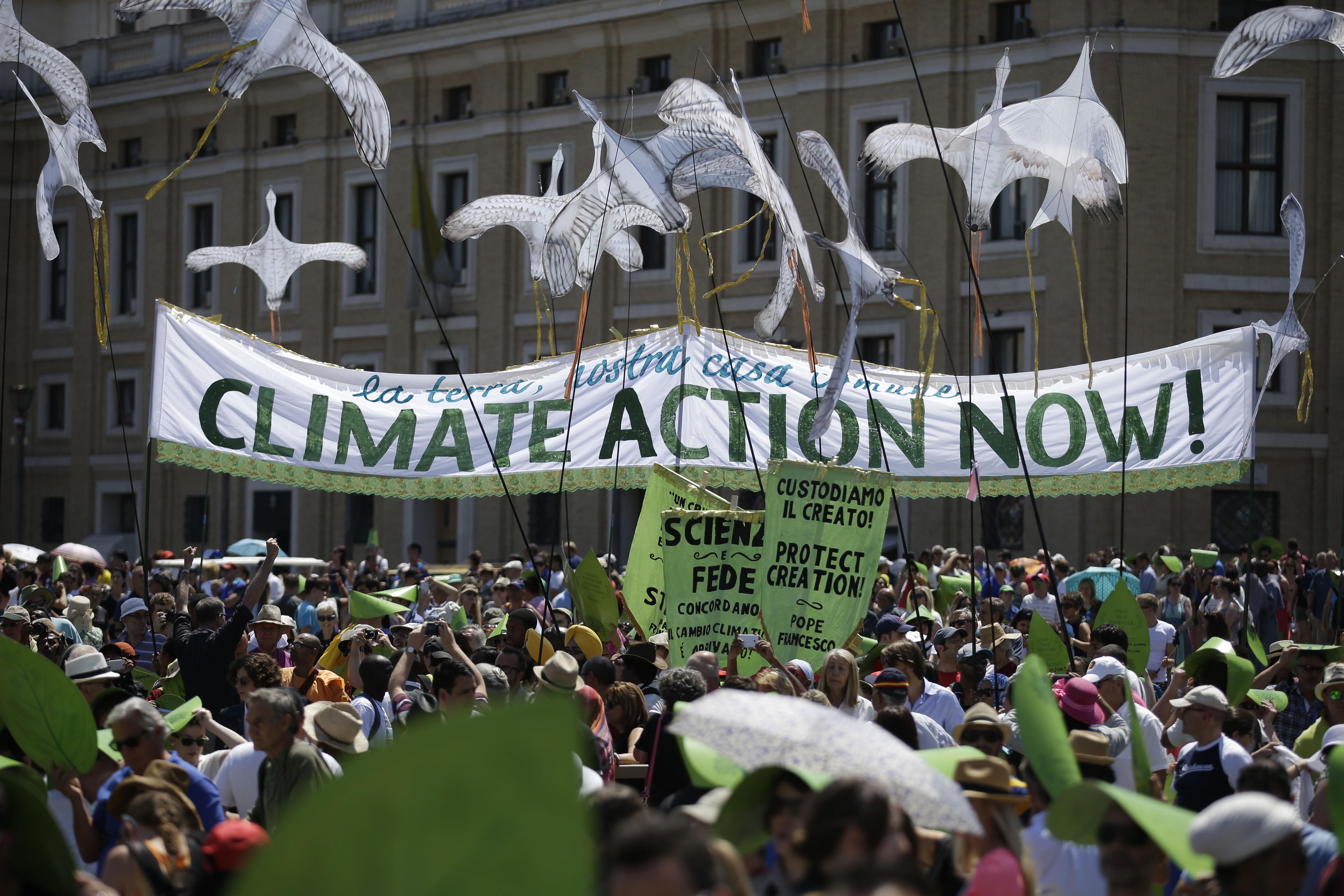 Une foule de manifestants, dont certains tiennent une banderole sur laquelle est écrit « Climate Action Now ! »