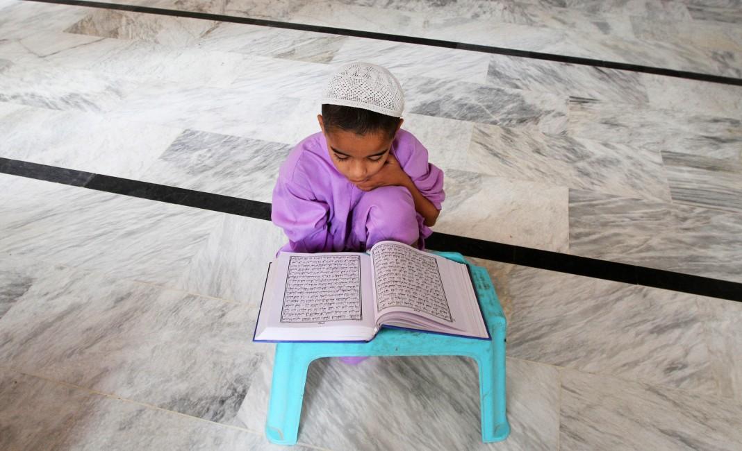 Un niño pequeño sentado en el suelo, estudiando un libro colocado en un atril (© AP Images)