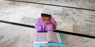 Un jeune garçon assis par terre, lisant le coran posé sur un tabouret (© AP Images)