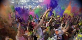 Des gens se jettent à la figure des pigments de peinture de toutes les couleurs. (© AP Images)