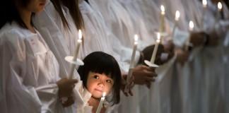 Niña en fila con personas de blanco llevando velas (© AP Images)