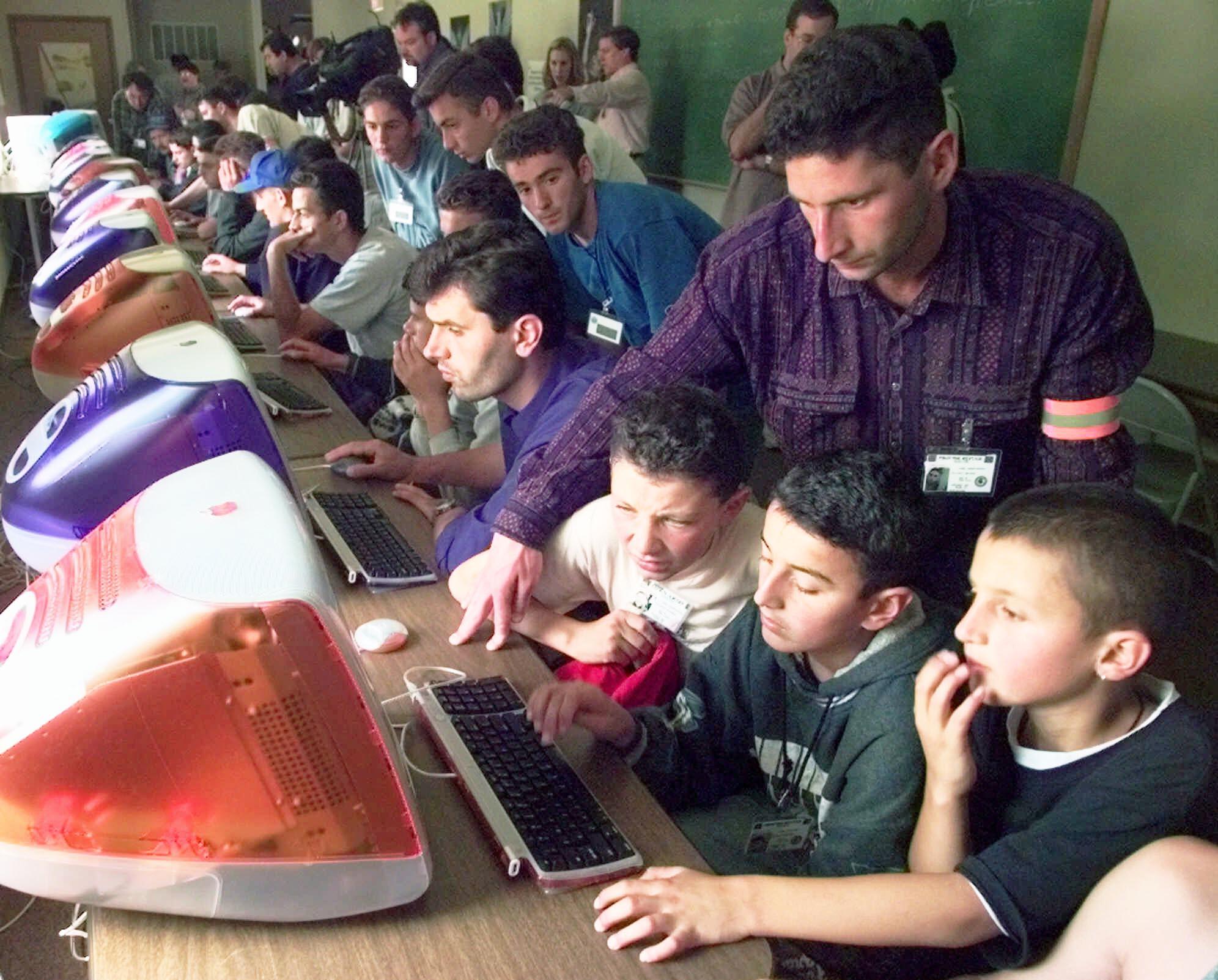 Un homme qui apprend à des garçons à se servir d'un ordinateur (© AP Images)