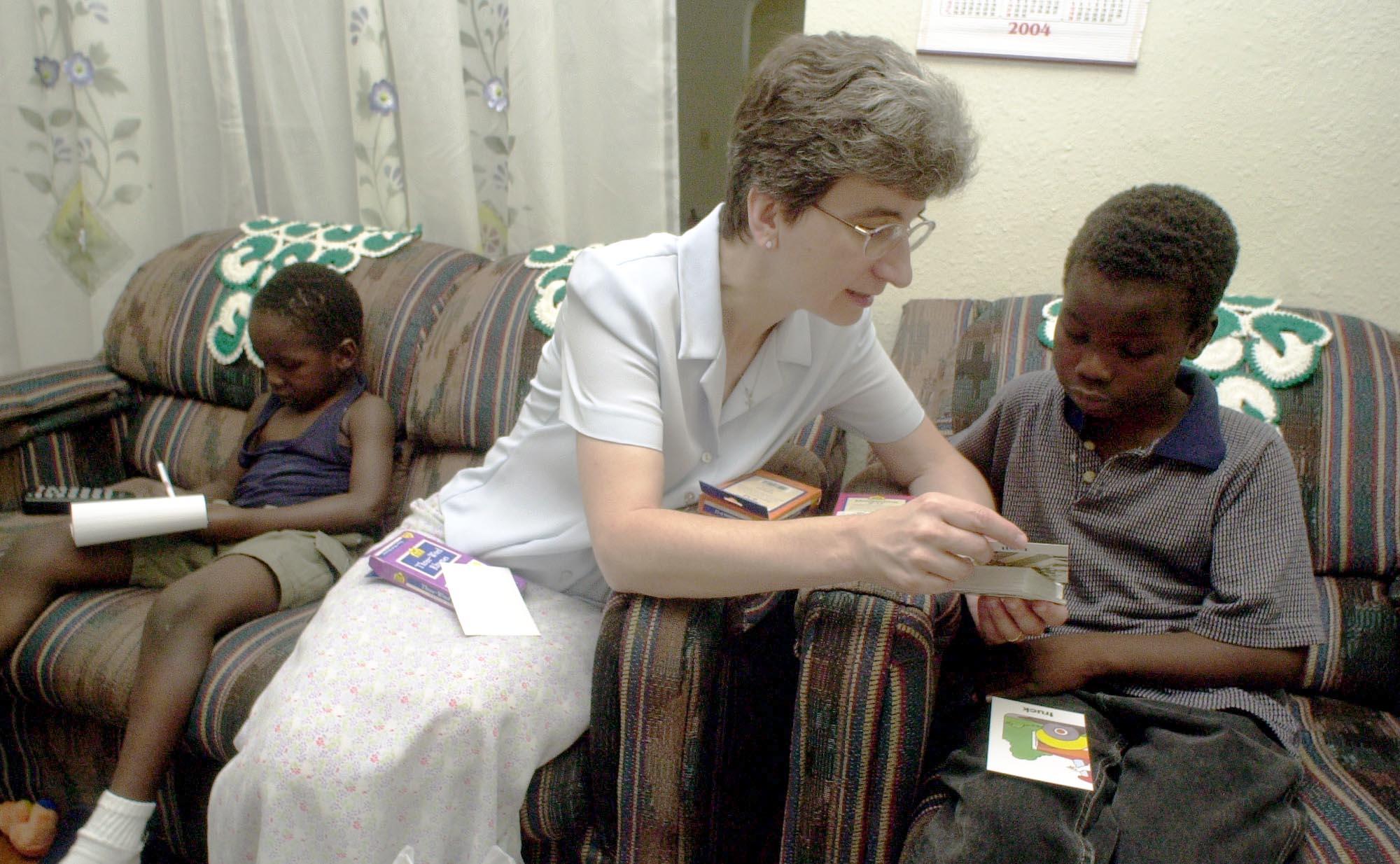 Une femme qui apporte un soutien scolaire à un jeune, assis sur un divan (© AP Images)