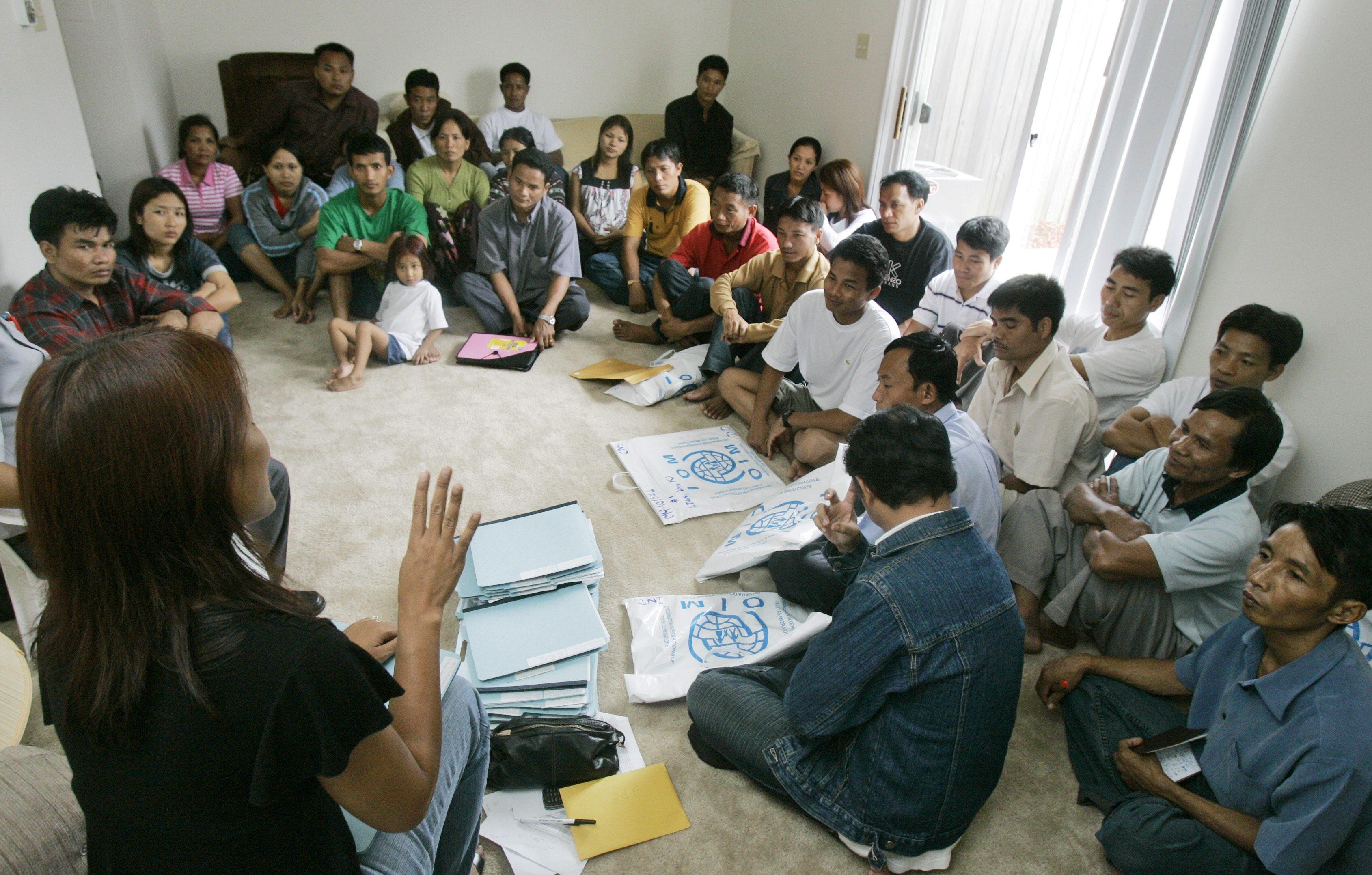 Une personne qui parle à un groupe de réfugiés birmans, assis par terre dans une pièce (© AP Images)