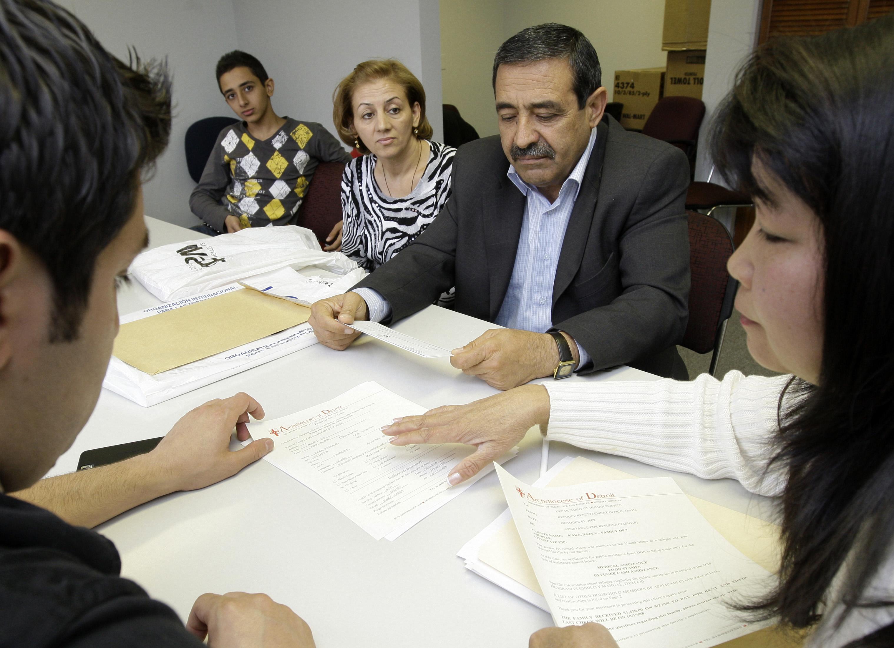 Un groupe de gens assis autour d'une table, en train d'examiner des papiers (© AP Images)