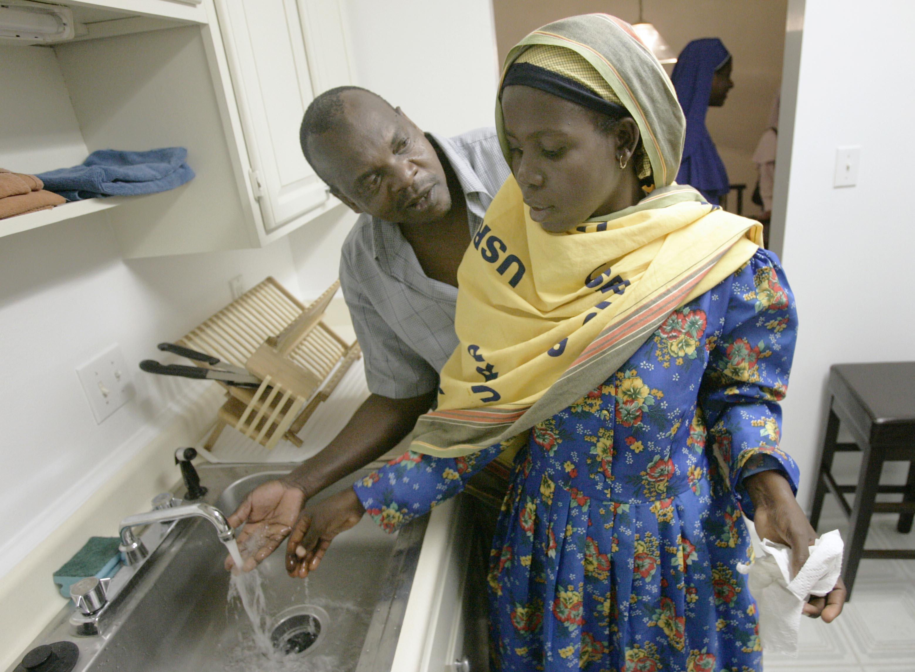 Un homme qui montre à une Somalienne comment fonctionne un robinet (© AP Images)