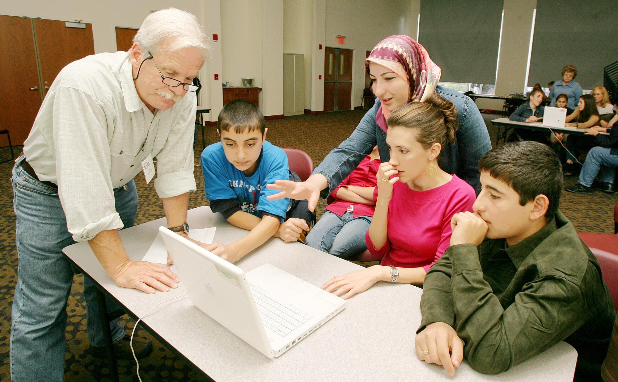 Un homme debout devant un ordinateur portable, avec des élèves à côté (© AP Images)