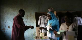 رای دهندگان با ناظر انتخاباتی که مراقب است (عکس از آسوشیتدپرس)
