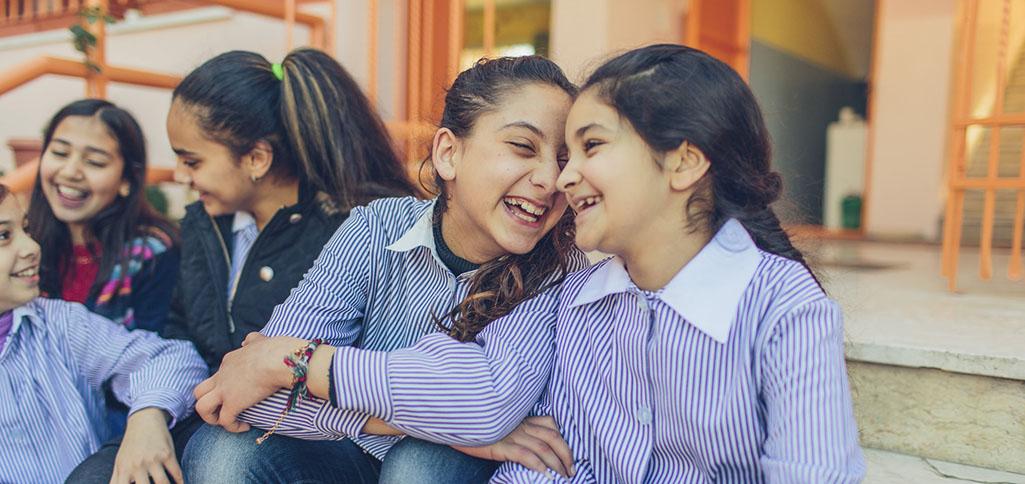 Niñas escolares sonriendo (USAID/Bobby Neptune)