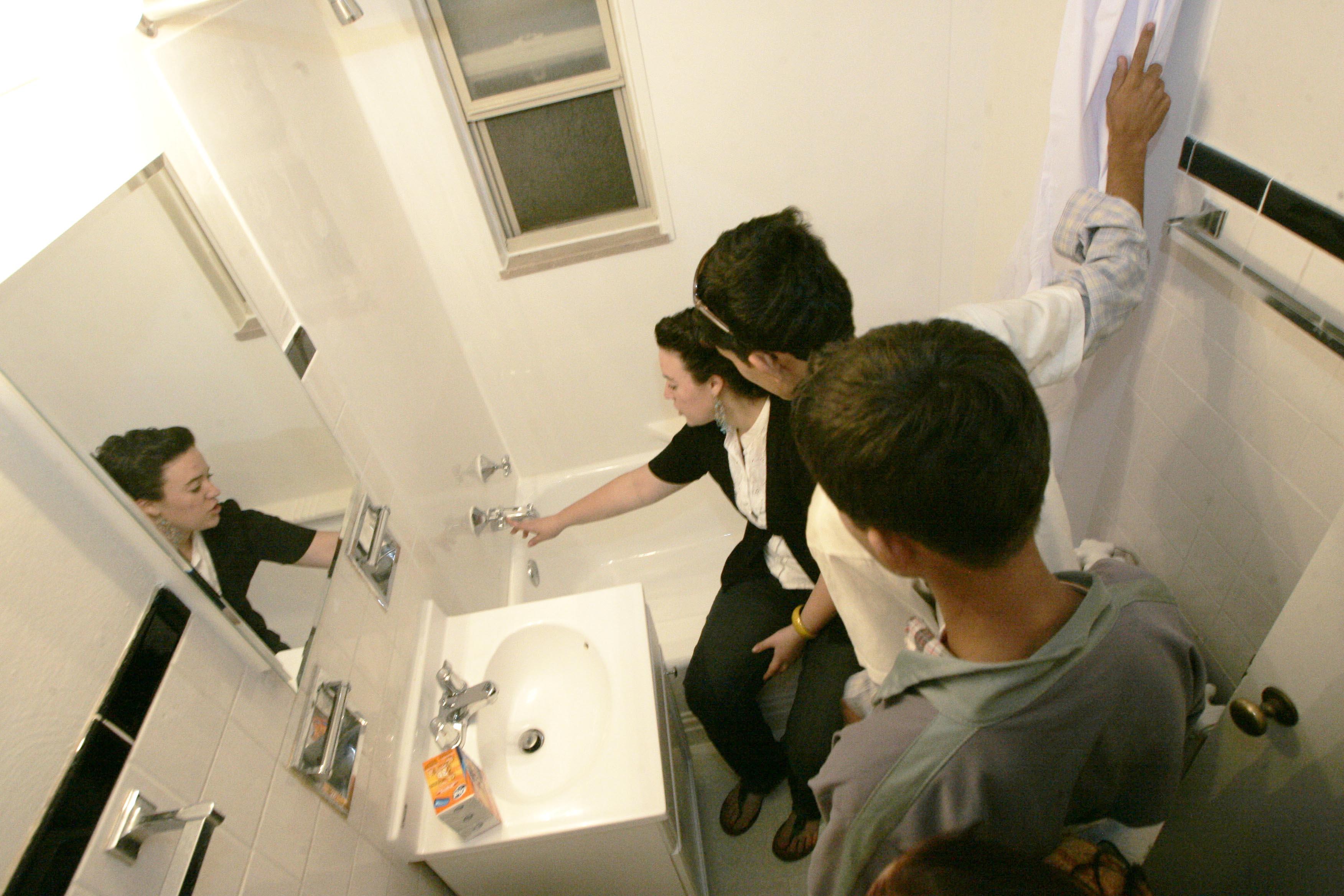 Une assistante sociale qui explique à deux réfugiées comment marchent une douche et une baignoire (© AP Images)