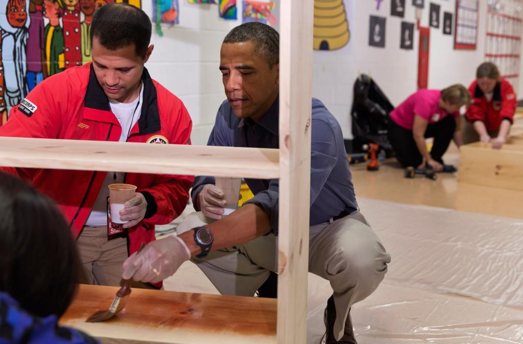 Jeff Franco et Barack Obama en train de vernir une étagère dans une école.