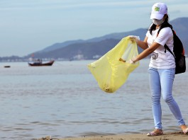 Young woman with face mask on beach, collecting trash in plastic bag (Shutterstock)