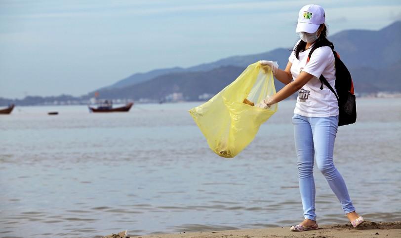 Une jeune femme, un masque sur le visage, ramasse des déchets sur une plage et les place dans un sac en plastique (Shutterstock)