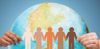 Illustration de personnes qui se tiennent la main tout autour de la Terre (Shutterstock)