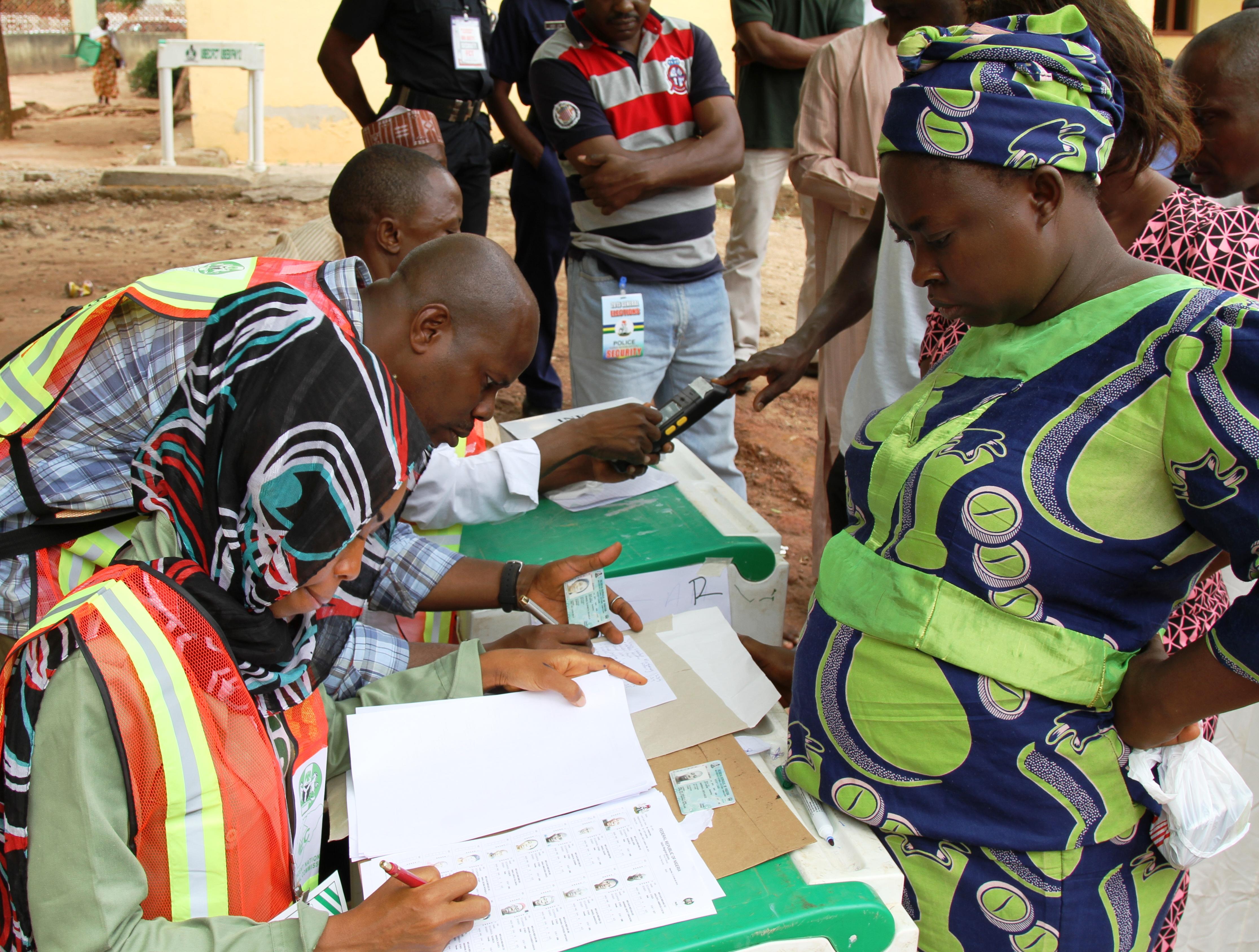 Une femme debout regarde un autre femme, assise à une table, en train de noter des choses sur une feuille. (Ambassade des États-Unis au Nigeria/Idika Onyukwu)