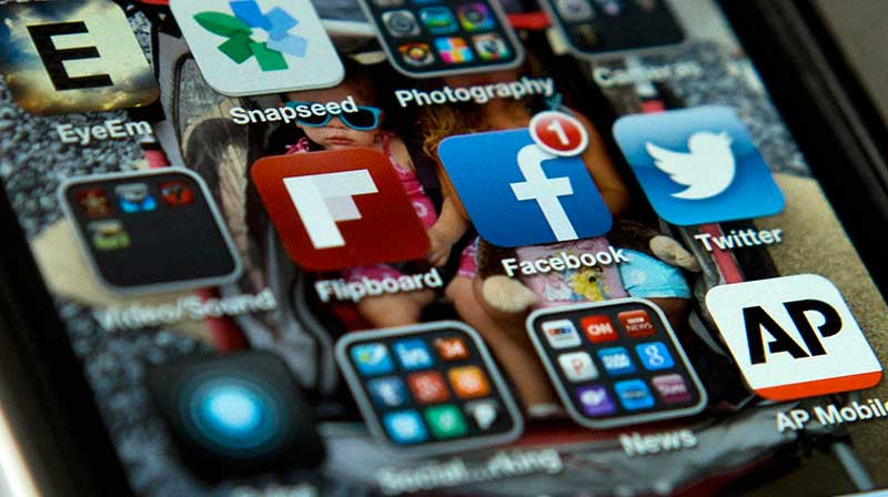 Smartphone screen showing social media icons (© AP Images)