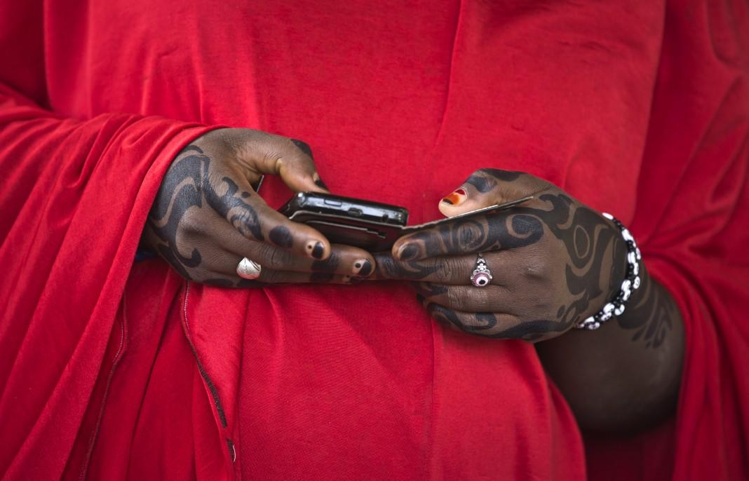 Des mains décorées au henné manipulent un téléphone portable. (© AP Images)