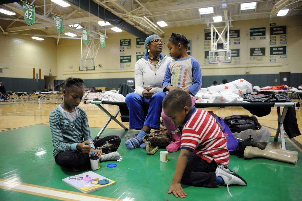 一个非洲裔美国家庭暂住在一个作为风暴天气安置所的学校体育馆内