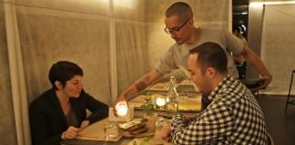 Deux personnes assises dans un restaurant regardent leur serveur verser la cire fondue d'une bougie dans un petit récipient posé sur la table. (© AP Images)