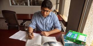 Un joven sentado a una mesa con muchos libros abiertos (Depto. de Estado/D.A. Peterson)