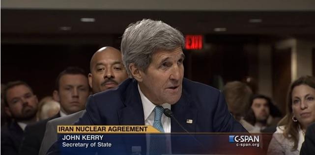 John Kerry speaking into microphone, TV titles at bottom (C-SPAN)