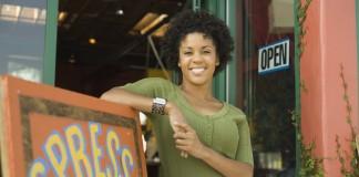 زنی خندان که به یک علامت کسب و کار تکیه داده است (© Jupiter Images/Thinkstock)