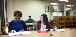 دانشجویان پشت میز کتابخانه نشسته و مطالعه می کنند. (وزارت امور خارجه/ دی ای پیترسون)