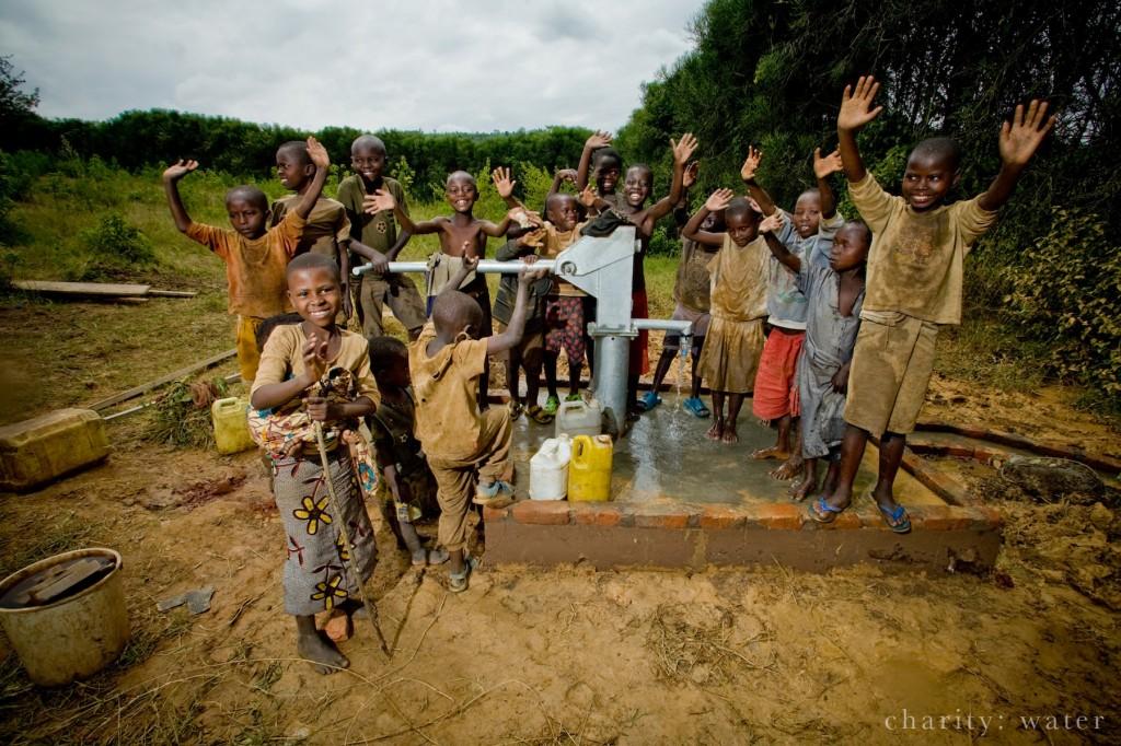 卢旺达一个村庄里的孩子们围在一个水泵旁