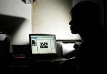 Woman in shadows looking at glowing laptop screen (© AP Images)