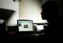Uma mulher no escuro olhando a tela do computador (© AP Images)