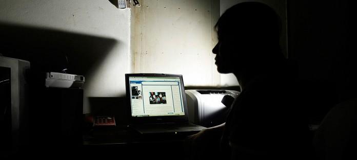 دختری در تاریکی به صفحه یک لپ تاپ خیره شده است. (عکس از آسوشیتدپرس)