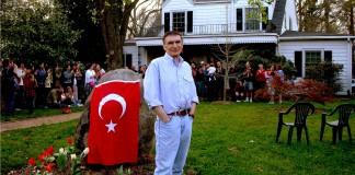 Au premier plan, Aziz Sancar pose dans un jardin, à côté d'un rocher recouvert d'un drapeau turc. Au second plan, un grand nombre d'étudiants en train d'applaudir (Crédit photo : AGS Foundation/Carolina Türk Evi)