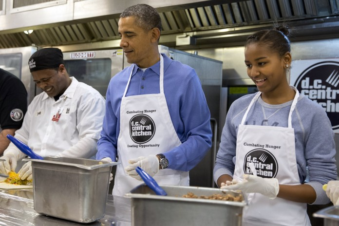 President Obama and daughter Sasha volunteering at D.C. Central Kitchen in Washington (© AP Images)