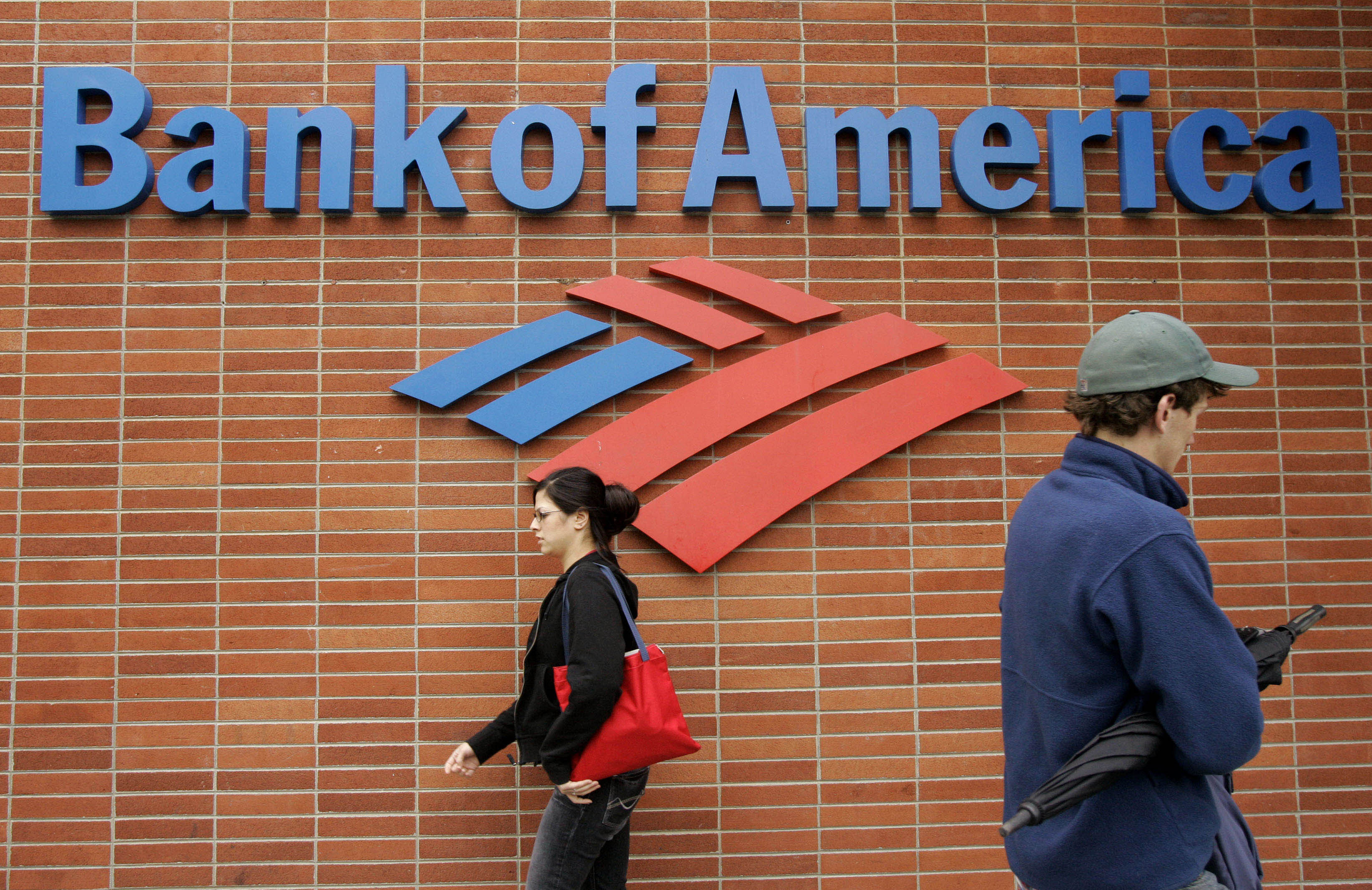 Pessoas andando perto de parede com o logotipo empresarial do Bank of America (© AP Images)