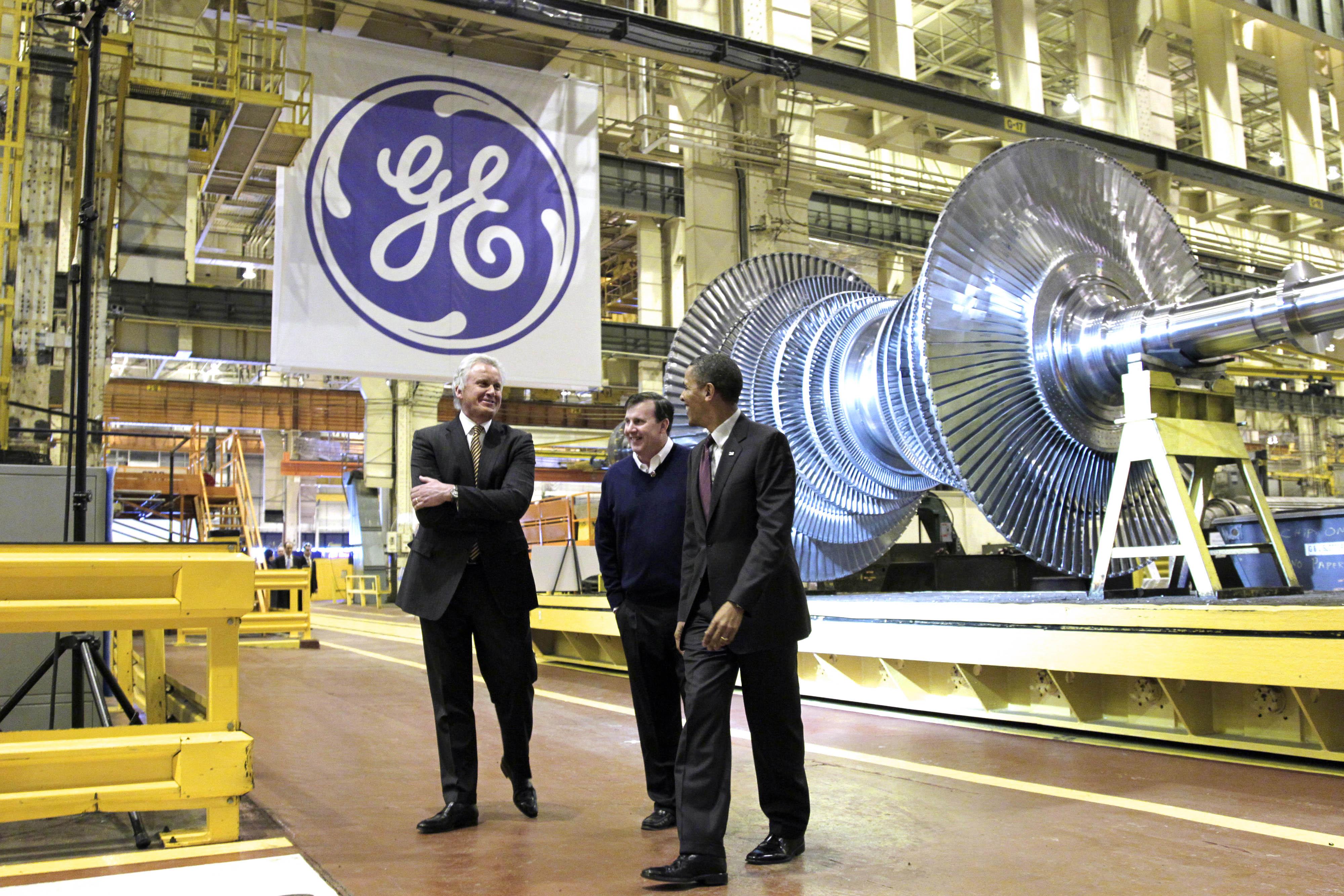 Pessoas de pé em fábrica com grande logotipo empresarial da GE pendurado no teto (© AP Images)
