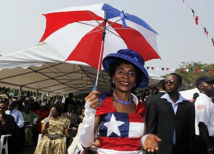 زنی با لباسی به رنگ های پرچم لیبریا چتر باز شده ای را در دست دارد (عکس از آسوشیتدپرس)