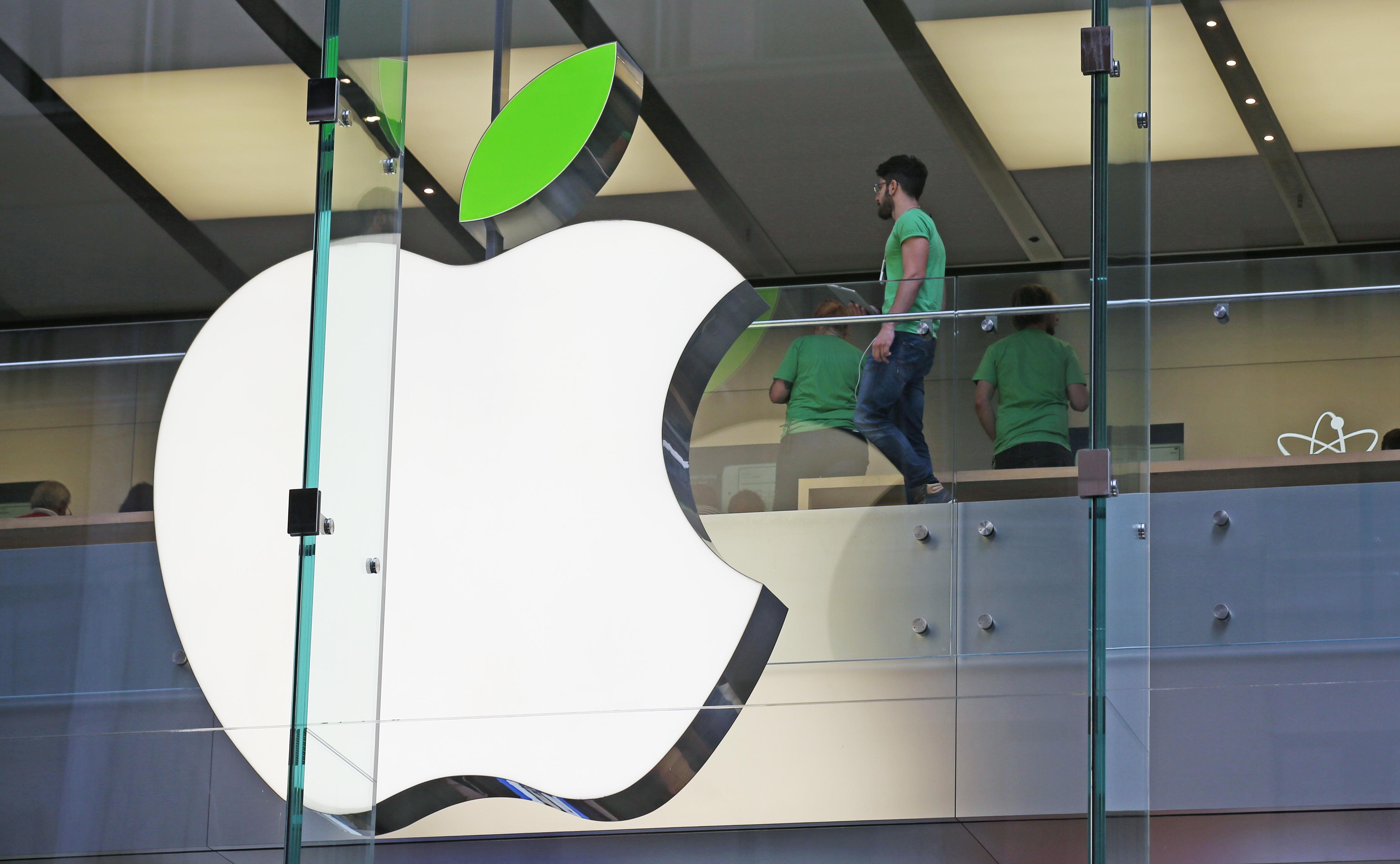 Pessoas próximas a grande logotipo empresarial da Apple (© AP Images)