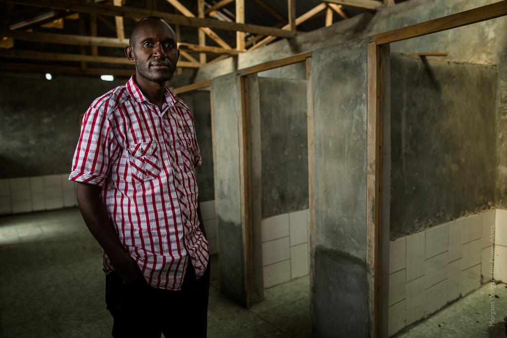 Amos Nguru, debout, à côté de toilettes en construction. (Morgana Wingard/PowerAfrica)