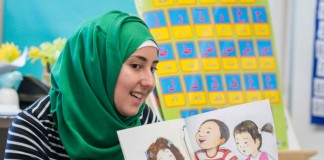 Une femme voilée tenant un livre devant des enfants (Crédit photo : AIMS)